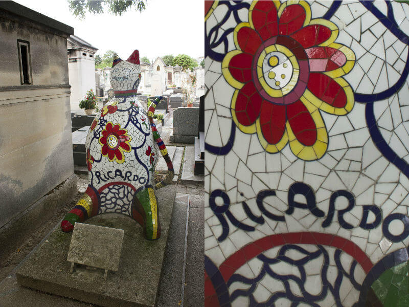 A six-foot tall mosaic cat statue in white, red, yellow, green and blue, marking a grave in the cemetery
