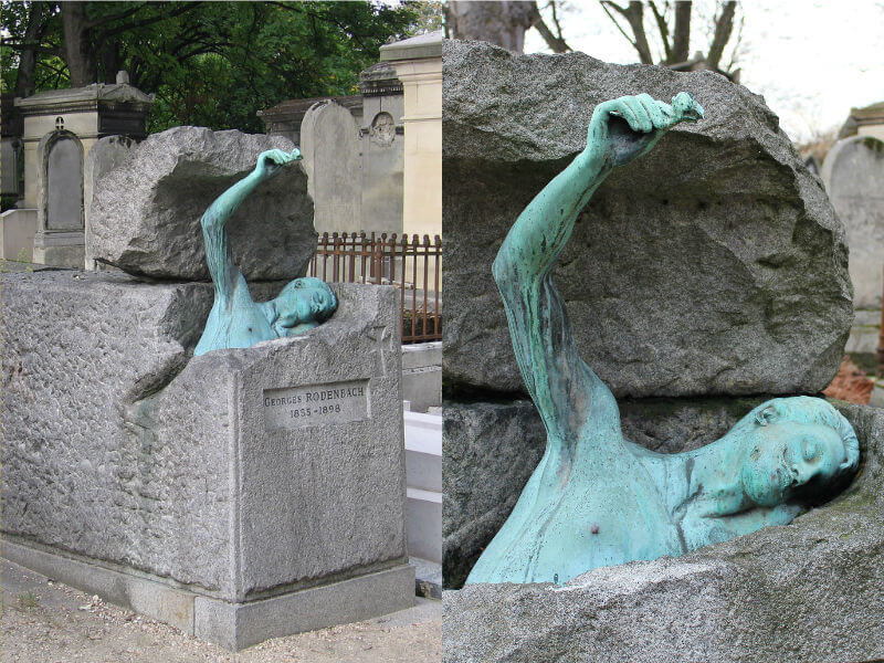 A stone grave with a bronze statue emerging from a crack, holding a rose in his hand