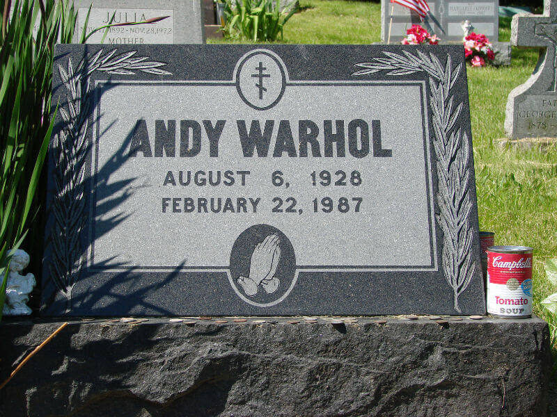 A granite gravestone, with a tin of Campbell's soup at the base