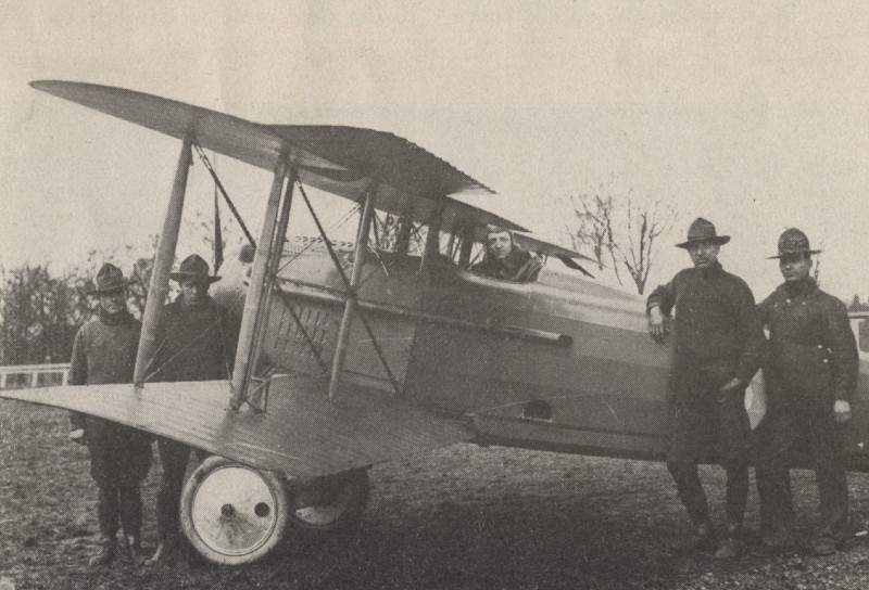 Black and white first World War of American pilot in a bi-plaine with other air crew standing around it in uniform