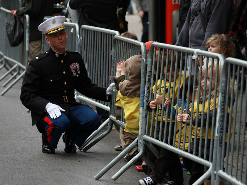 A member of the military meets with children during a Veterans Day parade