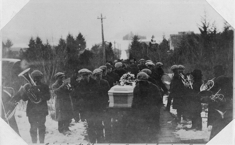 A funeral procession through the snow in Alaska, with a brass band accompanying the casket