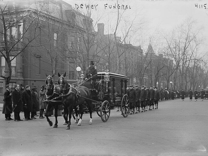 A horse-drawn hearse leaeding a funeral procession