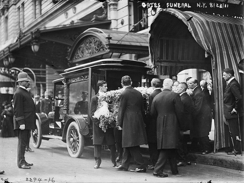 Pallbearers carrying a casket to a motor hearse