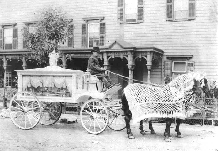 A horse-drawn hearse outside a funeral home