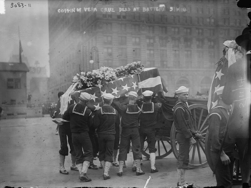 Sailors placing a casket draped in a US flag onto a wagon