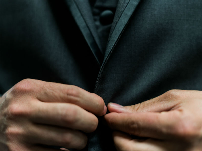 what to wear to a funeral -man buttoning funeral clothes