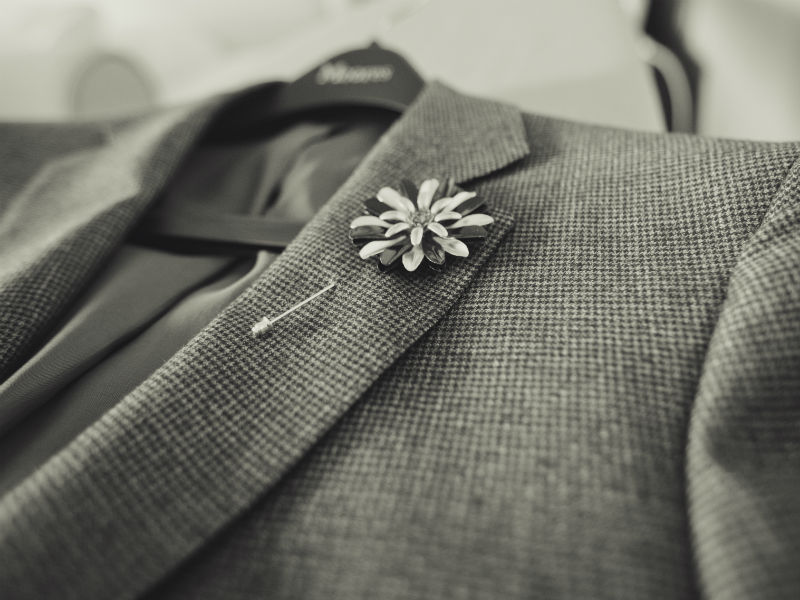 What to wear to a funeral- grey suit with floral motif pin