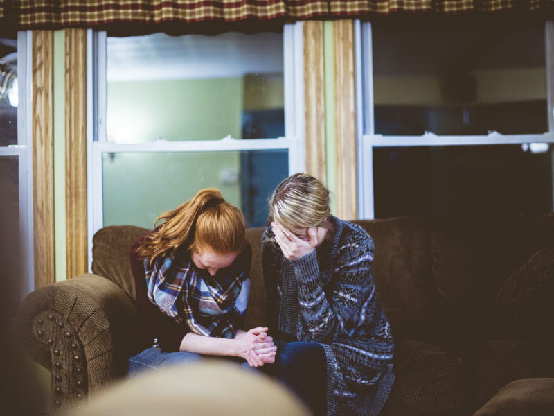 2 woman sitting on a sofa and crying